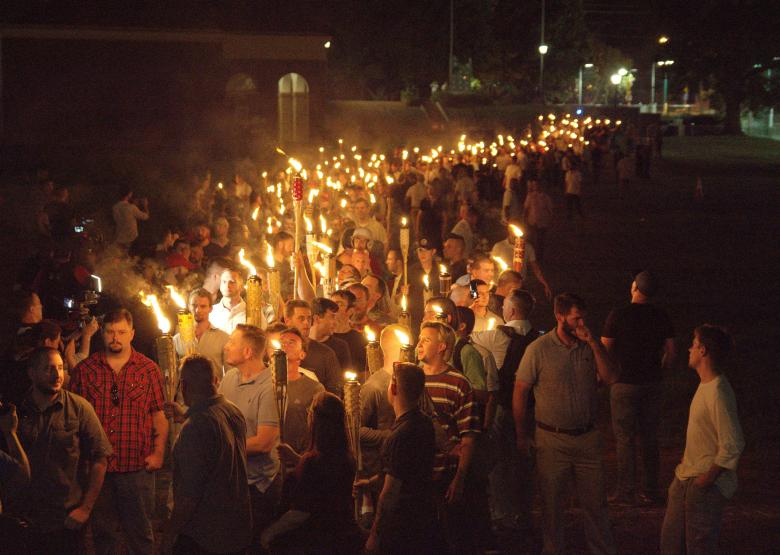 A torch-bearing mob marches in the darkness on a college campus.